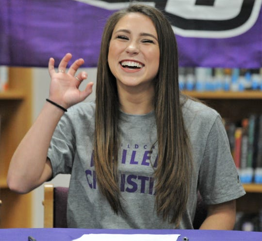 Merkel senior Kaydi Pursley makes the Abilene Christian hand sign at her signing ceremony Tuesday in the high school library.