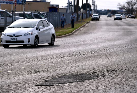 Vehicles travel along Sayles Blvd. near Cooper High School Tuesday. The deteriorating roadway there has long been a complaint of local motorists
