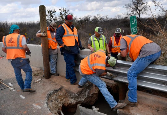 A city crew repairs a guardrail and fills in erosion at the Elm Creek bridge on Rebecca Lane on Friday.
