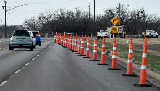Traffic cones guide motorists into merging to the left lane Friday as city workers repair part of the road around the bend on Rebecca Lane Friday.