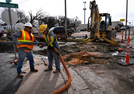 Dillon Walter (right) assist Jeremy Trevino with a vacuum attachment for siphoning water out of a hole at Butternut and S. 9th streets Tuesday. The men work for Elm Creek Plumbing and are replacing water lines along Butternut before the city begins construction on the roadway surface.