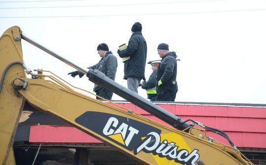 Investigators were on the roof Tuesday as they inspected the fire damage at the Econo Lodge in Battle Creek.