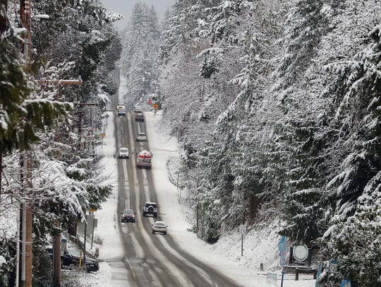 Vehicles travel along a snowy Fairgrounds Road in Central Kitsap on Tuesday.