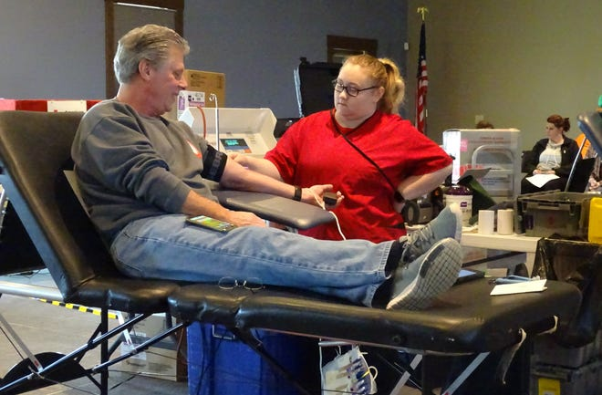"""Dana Biederman donates blood as Kyndra Williams checks his progress Tuesday morning at the """"A Pint for a Pint"""" blood drive at the Hord Family Farms office on Ohio 98."""