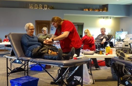 "Zachary Torocsik of the Red Cross prepares to draw blood from Kathy Bushey on Tuesday morning during the ""A Pint for a Pint"" blood drive at the Hord Family Farms office on Ohio 98."
