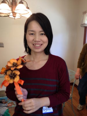 At the end of the Rising Sun Friends workshop, Nozomi Akatsuka shows her bouquet of handcrafted flowers made with dried slices of sweet potato glued on pine cones.
