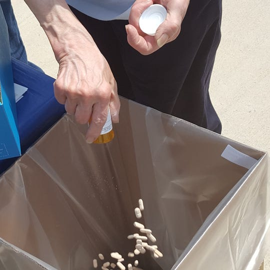 Someone drops unused prescription pills into a box during a DEA Drug Take Back day. The proper disposal is encouraged so that opioids and other potentially harmful medications don't get misused.