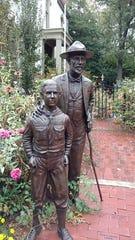 A statue of Daniel Carter Beard and a boy scout stand near the entrance of Beard's boyhood home in Kentucky.