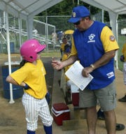 As a 10-year-old in 2005, Marylynn Muldowney gets some advice from her dad, Jim, during a North Brunswick Little League game
