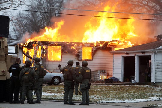 Local members of law enforcement at the scene as flames are visible from the home of a West Burlington resident involved in a hours-long standoff, Monday Jan. 13, 2020 at 414 E. Pennington St. in West Burlington, Iowa. The standoff began at about 2:40 a.m. Monday, when members of the West Burlington Police Department, Burlington Police Department and the Des Moines County Sheriff's office were called to the residence after a person had discharged a weapon inside the home. [John Lovretta/thehawkeye.com]