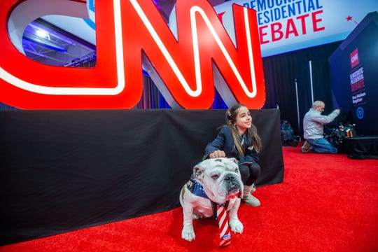 Lila Desai, 8, poses for a photo with Drake University mascot Griff before the CNN/Des Moines Register Democratic presidential debate Tuesday, Jan. 14, 2020.
