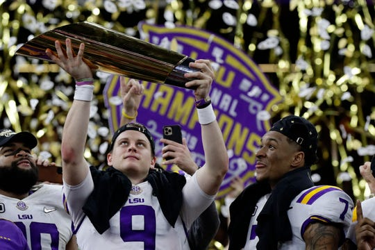 LSU quarterback Joe Burrow holds the trophy, as safety Grant Delpit looks on, for winning the National Championship on Monday night over Clemson in New Orleans.