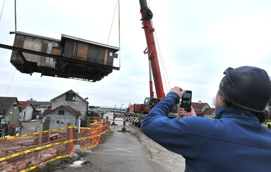 David Kareck, owner of the Village Cheese shanty, takes video of the shanty being lifted by crane off Leland's Fishtown docks and placed in the nearby marina parking lot. The waterlogged and rotting foundation will  be replaced and the shanty will return to it's site by April.