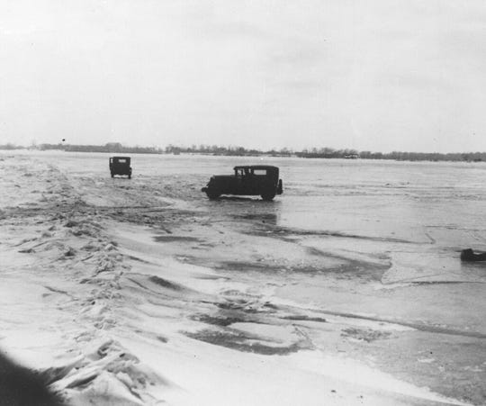 In this Feb. 14, 1930, file photo large quantities of Canadian beer and whisky are being transported in cars from Amherstburg, Ont., Canada, across the frozen lower Detroit River, to the Michigan side of the international boundary line. The cars are driven with one door open, so if the car goes through the ice the driver can scramble free.