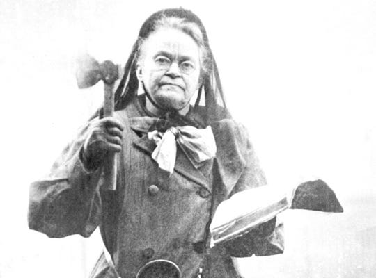 In this 1910 file photo temperance leader Carrie Nation wields her hatchet and bible in 1910. Nation has destroyed more than a few saloons with her hatchet.