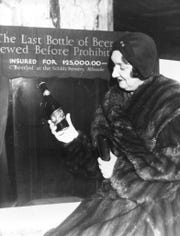 In this Dec. 29, 1930, file photo Rae Samuels holds the last bottle of beer that was distilled before prohibition went into effect in Chicago. The bottle of Schlitz has been insured for $25,000.