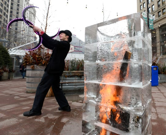 Eric Scott Baker of Detroit spins lighted s-staffs behind a Fire and Ice Tower. Baker is a performer with the Detroit Circus.