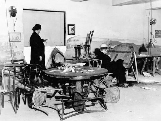 """In this Dec. 31, 1931, file photo the wrecked speakeasy in the Hotel Victoria in mid-Manhattan, where Louis Levine, alias Louis Taylor, a small-time gambler, was killed by one of three gunmen earlier in the day in New York. A bystander points to a bullet hole in the wall, while another is seated in the chair where Levine, known as """"Crooked Neck Louie"""", was gambling when he was shot."""
