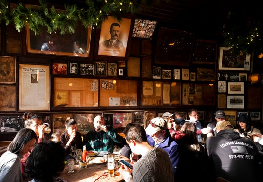 In this Dec. 27, 2019 photo, customers sit beneath vintage photos and documents, including a poster of Vice President Theodore Roosevelt, in McSorley's Old Ale House in New York.