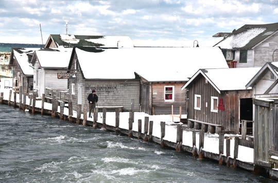 Record-high water levels in the Leland River in Leland, Michigan have caused flooding and damage to fishing shanties along the river's banks. The Morris Shanty, center with red banner, is scheduled to be lifted off its unstable foundation and saved this  winter.
