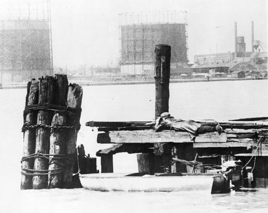 In this April 28, 1929, file photo a rum runner in Windsor, on the Canadian side of the Detroit River, watches with field glasses for lookout on the American side to signal that no prohibition agents are in sight. His outboard motorboat, loaded with illegal liquor, is shown beneath pilings.