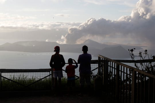 People watch from Tagaytay, Cavite province, south of Manila, as Taal Volcano continues to spew ash on Tuesday.