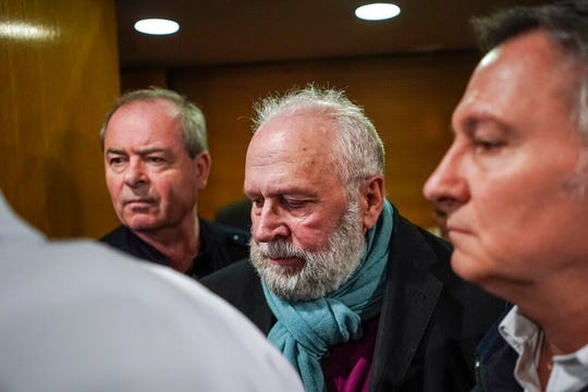 Former French priest Bernard Preynat, center, arrives at the Lyon court house, central France, Monday Jan.13, 2020. Bernard Preynat, is accused of sexually abusing some 75 Boy Scouts went on trial Monday -- but the proceedings were delayed until Tuesday because of a strike by lawyers.