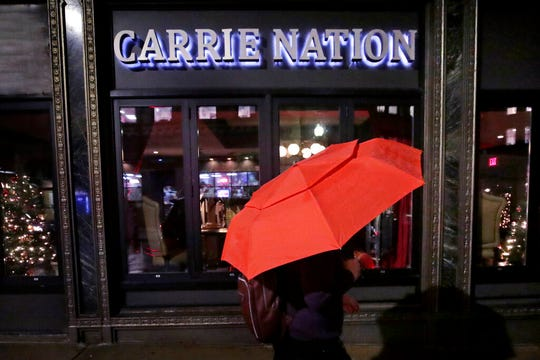 In this Dec. 10, 2019, file photo a woman holding an umbrella passes the Carrie Nation lounge in Boston, titled after the namesake of the woman supporting the temperance movement prior to the 1920 Prohibition ban on alcohol.