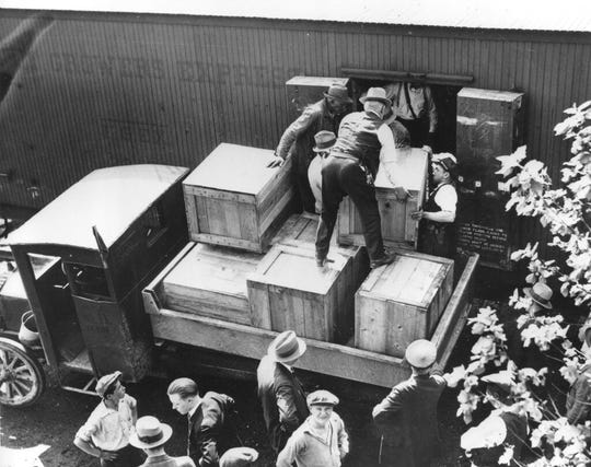 In this May 15, 1929, file photo authorities unload cases of whiskey crates labeled as green tomatoes from a refrigerator car in the Washington yards.