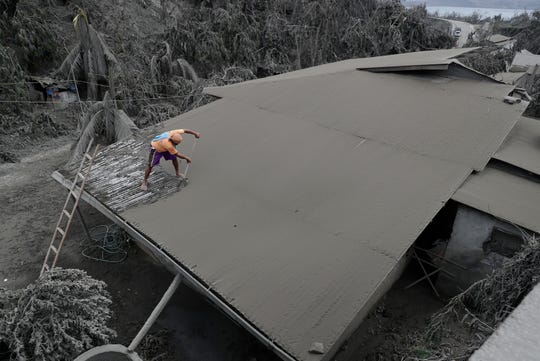 A resident clears volcanic ash from his roof in Laurel, Batangas province, southern Philippines on Tuesday.