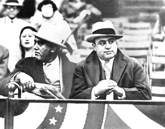 In this Oct. 10, 1931, file photo Al Capone, Chicago gangland, right, attends a game between Notre Dame and Northwestern Grid in Chicago. Former Alderman A.J. Prignano is on the left. Capone earned tens of millions of dollars annually from bootlegging and speakeasies.
