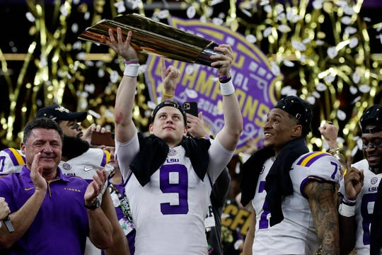 LSU quarterback Joe Burrow holds the trophy as safety Grant Delpit looks on after a NCAA College Football Playoff national championship game against Clemson. LSU won 42-25.
