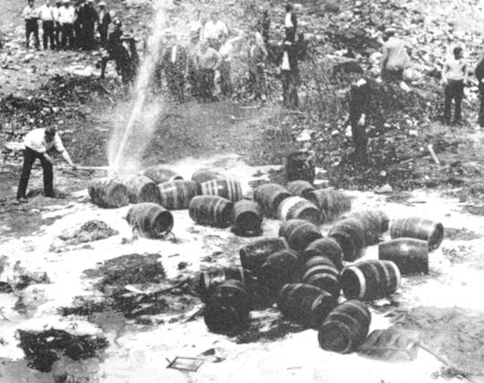 In this June 18, 1931, file photo beer barrels are destroyed by prohibition agents at a dump in New York City.