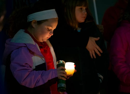 Neighbor and friend Miley Wire, 11, stares into the candlelight during a vigil for slain Evansville  3-month-old Kieran Bengert  Monday evening, Jan. 13, 2020.