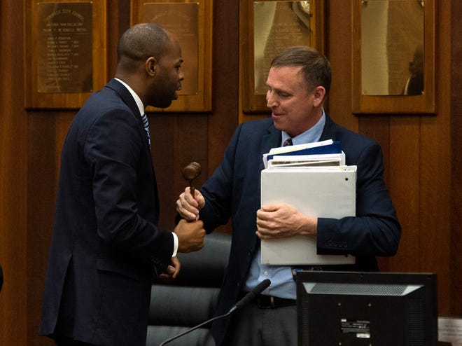 City Councilor Alex Burton, left, receives the gavel from Councilor Jim Brinkmeyer, right, after being elected president of the panel for 2020 in a 6-3 decision Monday evening, Jan. 13, 2020.