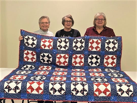 Donna Foss, left, stands with former Navy WAVE Terry Stamm, center and  Deb Huffman.  Both Foss and Huffman made the quilt with Leah Coffey, who are all members of Hayes Ohio Star Quilt Guild, Fremont, to present to Stamm.