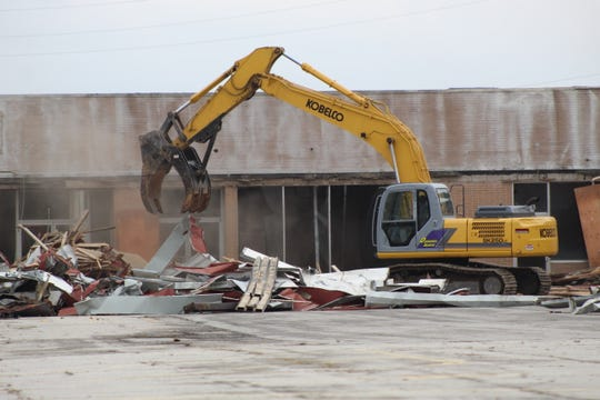 Demolition crews tear down several dilapidated buildings at the former East Side Plaza, 1791 E. State St. Monday.