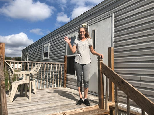 Rescue Cats Rock founder Tammy Nemec waves from the porch of the new mobile home she'll share with her rescued cats. She bought the North Fort Myers home last week.
