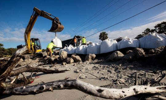 A crew from B.J. Excavating installs temporary  emergency sand bags along Sanibel-Captiva Road just before Blind Pass on Sanibel on  Tuesday Jan.14, 2020. Sanibel officials are worried that erosion will make the road collapse. The company is placing 100 one-ton bags along the beach and roadway.