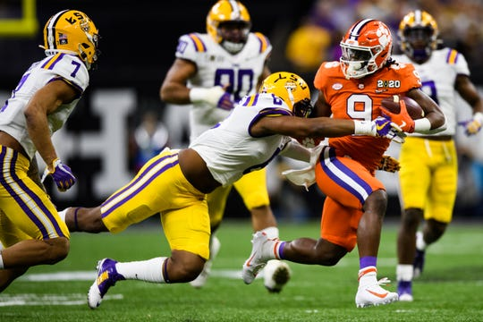 Clemson running back Travis Etienne (9) attempts to evade LSU linebacker Jacoby Phillips (6) during the College Football National Championship game at the Mercedes Benz Superdome Monday, Jan. 13, 2020.