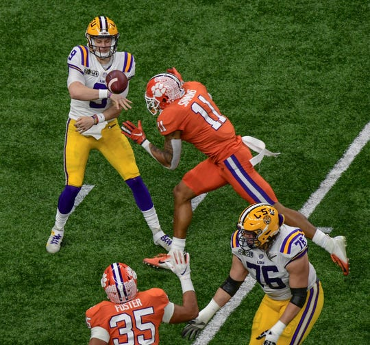 LSU quarterback Joe Burrow (9) throws near Clemson safety Isaiah Simmons (11) during the first quarter at the Mercedes Benz Superdome in the National Championship football game in New Orleans Monday, January 13, 2020.