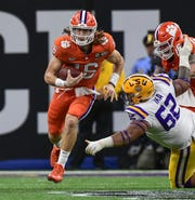 Clemson quarterback Trevor Lawrence (16) runs by LSU defensive Siaki Ika (62) during the second quarter of the National Championship game at the Mercedes Benz Superdome in New Orleans Monday, January 13, 2020.