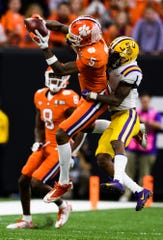 Clemson wide receiver Tee Higgins (5) attempts to catch the ball as LSU defensive back Kristian Fulton (1) attempts to take him down during the College Football National Championship game at the Mercedes Benz Superdome Monday, Jan. 13, 2020.