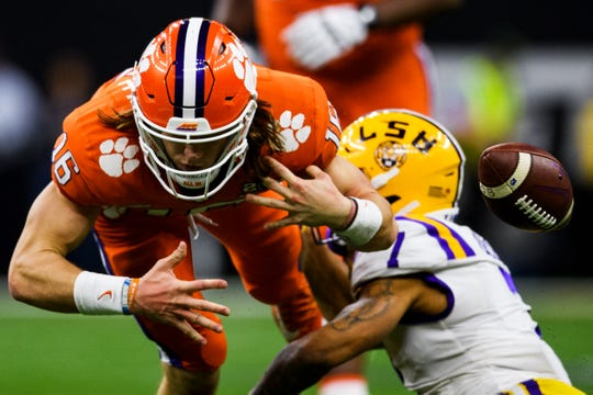 Clemson quarterback Trevor Lawrence (16) fumbles the ball after getting hit by LSU defensive back Grant Delpit (7) during the College Football National Championship game at the Mercedes Benz Superdome Monday, Jan. 13, 2020.