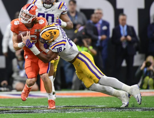 Clemson quarterback Trevor Lawrence (16) gets tackled by LSU linebacker K'Lavon Chaisson (18) during the fourth quarter of the National Championship game at the Mercedes Benz Superdome in New Orleans Monday, January 13, 2020.