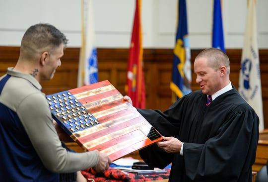 Great Falls Veterans Treatment Court graduate Benjamin Fontana gifts plaque to Judge Greg Pinski during Tuesday's treatment court graduation ceremony.