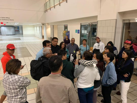 Speaker Tina Muna Barnes, Guam airport officials and representatives of the Filipino Community of Guam meet with stranded Manila-bound passengers Monday night.