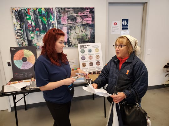 Lori Kistler, right, of Rantoul gets an in-line consultation before picking up her order of edibles from NuMed Urbana on Jan. 10, 2020. Kistler, 58, is a first-time purchaser of legal marijuana who has considered trying medical marijuana for years. She said she is happy about legalization because it allows her to easily try marijuana to see if medicinal options may be right for her.