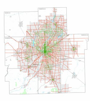 This map of central Indiana shows existing sidewalks on main roads in green, and the red lines are gaps in pedestrian infrastructure.