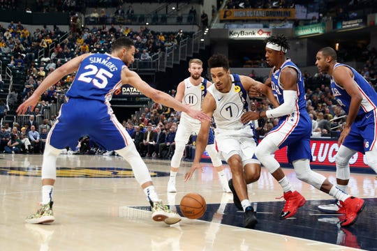 Jan 13, 2020; Indianapolis, Indiana, USA; Indiana Pacers guard Malcolm Brogdon (7) drives to the basket against Philadelphia 76ers guards Ben Simmons (25) and Josh Richardson (0) during the first quarter at Bankers Life Fieldhouse.